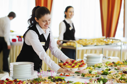 The waiters set the tables in the restaurant for the banquet